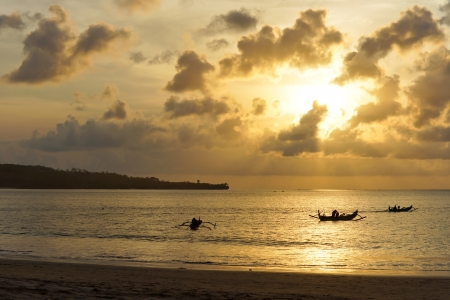 Three outrigger canoes silhouetted at dusk against the glowing surface of the sea under an orange marine sunset photo