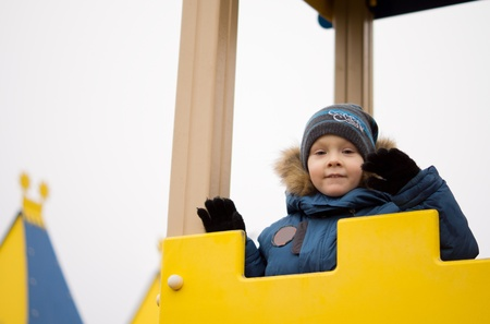 Playful young child in winter clothing standing on top of colourful yellow equipment in an outdoor kids playground photo