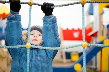 Young child wrapped up warmly against the winter weather playing on a climbing rope in a kids playground photo