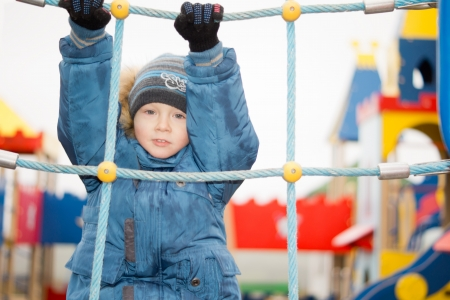 Cute little boy dressed up warmly against the winter cold hanging from ropes on a colourful childrens playground photo