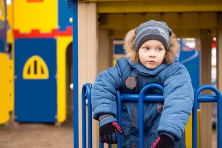 Adorable young child wrapped up warmly in thick winter clothes, cap and gloves playing in a colourful kids playground on a cold day photo