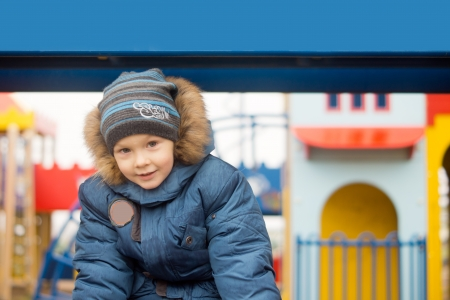 Young child warmly dressed against the cold winter weather playing in an outdoor playground photo