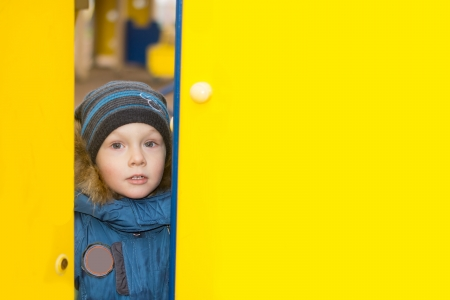 Kid peeping through a gap in two yellow walls at some kid photo