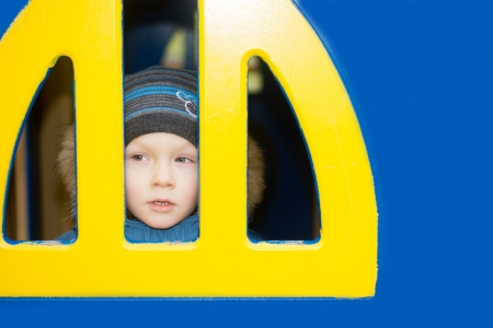 A kid looking from a yellow window on blue wall  photo