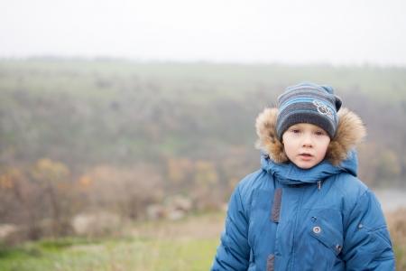 Hijo joven en un paisaje brumoso calurosamente vestido con una piel recortado chaqueta y la gorra contra el fr�o con copyspace