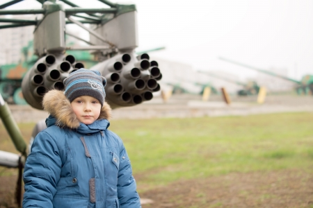 A cute kid posing in front of the cannons  photo
