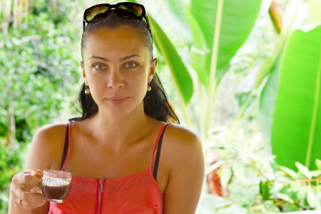 Portrait of a young woman drinking coffee with tropical background photo
