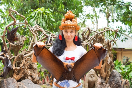 Woman in a headdress holding a large flying fox or fruit bat by the tips of its wings in a tropical garden environment