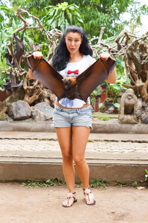 fruit eater: Shapely Asian woman in sandals and shorts holding a flying fox or large fruit bat with its wings outspread in a garden Stock Photo