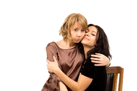 comforted: Attractive forlorn looking sad young woman being comforted by her friend who is smiling in an effort to cheer her up, on a white studio background