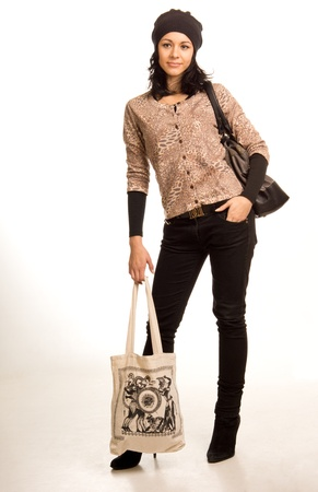 Beautiful stylish young woman out shopping posing in trendy tight fitting jeans and stillettoes with a handbag and cloth shopping bag isolated on white Stock Photo - 16692064
