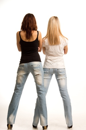 tight fitting: Back view of two sexy slender girls wearing tight fitting jeans standing side by side on a white studio background Stock Photo