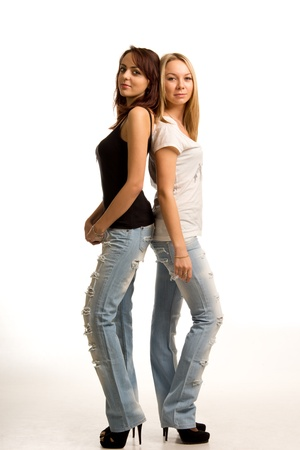 tight fitting: Two trendy young women in tight fitting jeans and stilettoes standing back to back, full length portrait isolated on white