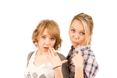 scepticism: Two beautiful young blonde girls expressing amused scepticism and surprise as they stand looking up at the camera isolated on white