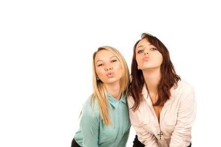 puckering lips: Two attractive mischievous young girls looking for a kiss standing close together pursing and puckering their lips, half body studio portrait isolated on white
