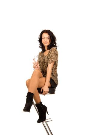 Mujer elegante hermosa que se sienta en un taburete de metal moderno bar disfrutando de una copa de champ�n mientras de fiesta, aislado en blanco