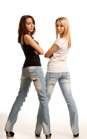 tight fitting: Sexy young women in tight fitting jeans standing side by side with their backs to the camera looking back over their shoulders isolated on white