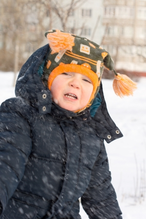 flurry: Cute little boy with a warm woolly cap with tassles caught in a flurry of snow drifting down past his face as snowflakes on a freezing winter day