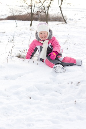 frolicking: Cute little girl with a beautiful smile wearing a cuddly punk outfit and cap frolicking in winter snow with copyspace Stock Photo