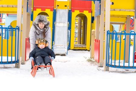 toboga: Mamma dando il suo giovane figlio di una discesa in slittino nella parte anteriore dell'apparecchio neve colorata di un parco giochi per bambini