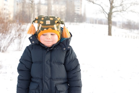 Cold little boy in winter snow giving a cautious smile for the camera as though unsure of whether he is enjoying the cold weather or not photo