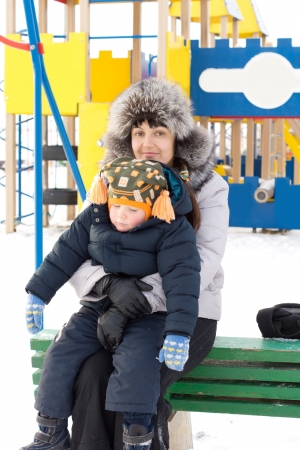 cuddled: Sleepy little boy being cuddled by his mother as they sit in cold winter snow in a colourful childrens playground