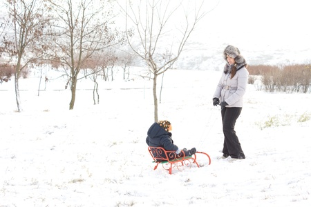 frolicking: Mother pulling her young son along on a colourful orange sled in a snowy winter field with copyspace