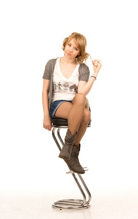 Pretty blonde woman in smart denim shorts and boots sitting on a contemporary metal bar stool, full length studio portrait isolated on white