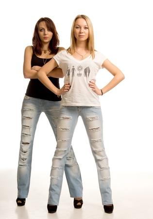 jeans apretados: Dos mujeres atractivas j�venes con actitud de pie lado a lado en la piel ajustados pantalones vaqueros de dise�o desiguales frente a la c�mara con las manos en las caderas o cruzados sobre el pecho aislado en blanco
