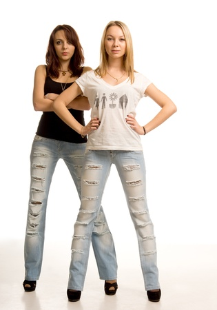 Two sexy young women with attitude standing side by side in skin tight ragged designer jeans facing the camera with hands on hips or folded across her chest isolated on white photo
