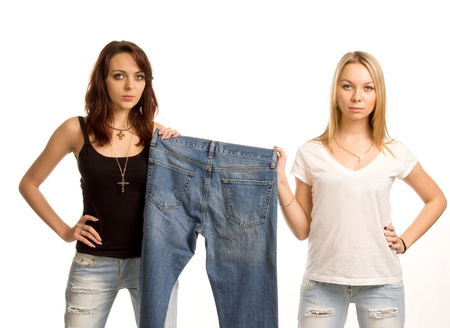 tight fitting: Two sexy young female friends in tight fitting raggedy designer jeans posing holding up a pair of old blue denim jeans on display, three quarter studio portrait isolated on white