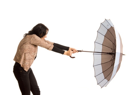 blown away: Woman battling with her umbrella holding on tightly as it is blown away by the wind, three quarter studio portrait isolated on white
