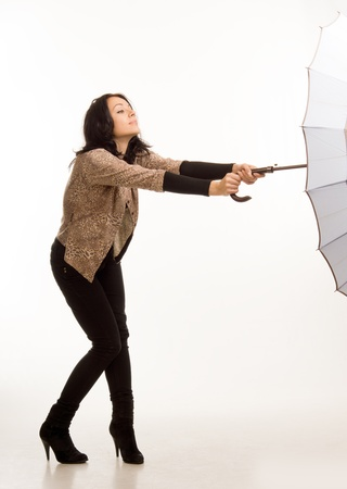 blown away: Attractive fashionable young woman struggling to control an umbrella on a windy day as it is caught by the wind and blown away, full length studio portrait isolated on white