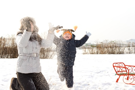frolicking: Mother and her young son frolicking in the winter snow throwing it up in the air so that the flakes drift down covering them