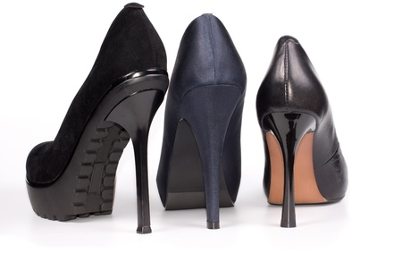 Back view of three ladies stiletto shoes in black suede and blue and black leather showing the height of the heels and soles on white Stock Photo - 17420139