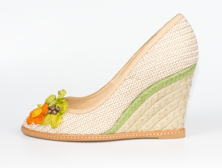 Pretty casual textile ladies shoe with a high wedge heel and floral ornament on the toe for everyday casual wear on white Stock Photo - 17420078