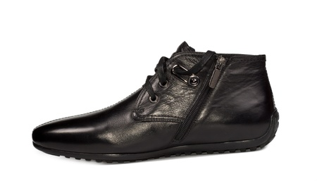 Side view of a mens comfortable flat black leather lace up ankle high shoe for everyday casual wear on white photo