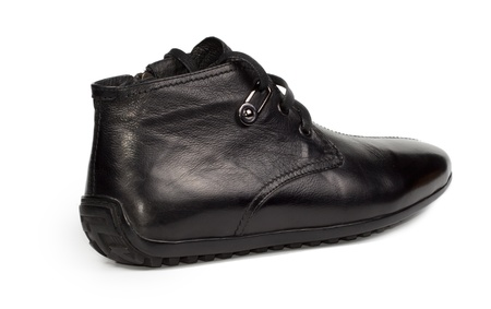 Angled rear view of a stylish mens casual black leather shoe with a flat sole and laces on a white background photo