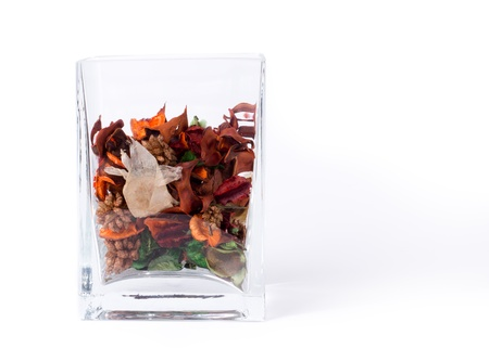 potpourri: Transparent rectangular glass container of fresh dried natural potpourri with flowers, leaves and spices for a fragrant interior aroma in the house on a white background Stock Photo