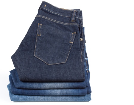 Neatly folded blue denim jeans with the pocket and stitching visible displayed on white photo