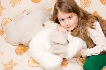 clutching: High angle view of a cute little girl lying on her bed cuddling a soft plush toy and looking up at the camera