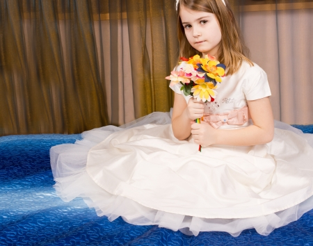 petticoat: Beautiful little girl posing sitting on the floor on a blue carpet in a tutu with the filmy gauze skirt spread out around her while she holds a bouquet of flowers in her hands