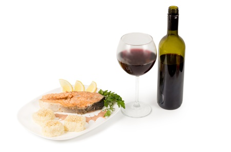 unlabelled: Tasty salmon steak served with an unlabelled bottle and full glass of red wine