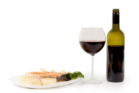 unlabelled: Serving of salmon and red wine in a wine glass with an unlabelled bottle alongside