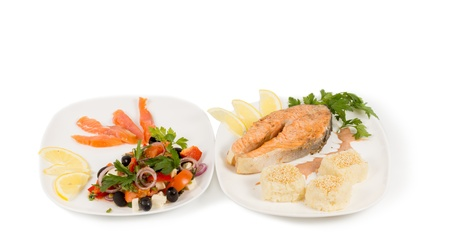 vitamin d: Cooked salmon steak and salad served on two seperate plates