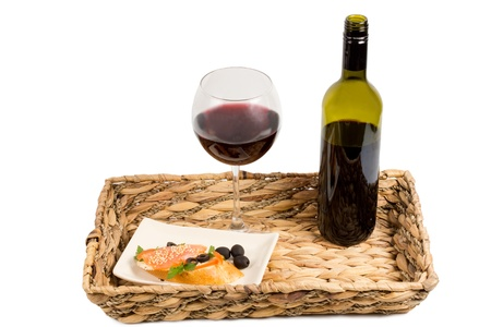 unlabelled: Grilled salmon steak and red wine in a glass and unlabelled bottle served on a rustic woven tray isolated on white