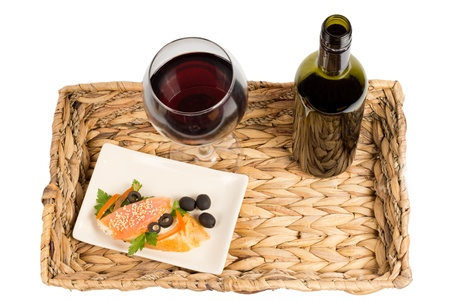 unlabelled: Overhead view of a tasty healthy meal of salmon steak served on a rustic woven tray with a glass and bottle of red wine Stock Photo