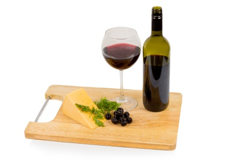 unlabelled: Delicious snack of a glass of red wine, cheese and black olives on a wooden board with an unlabelled wine bottle