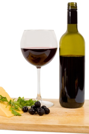 unlabelled: Unlabelled bottle of red wine with a full wineglass served with black olives and a wedge of cheese on a wooden chopping board isolated on white