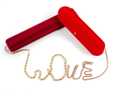 A gold chain for a loved one carefully arranged to spell the word LOVE with two luxury red gift boxes photo